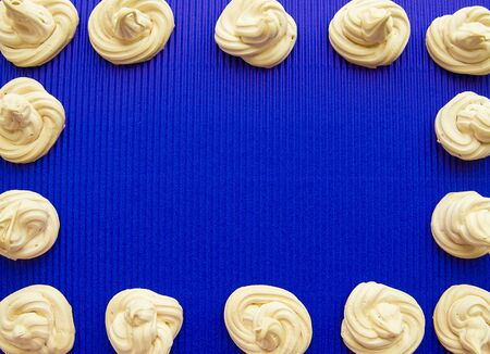 frame of meringue, meringue on a blue background Stock Photo