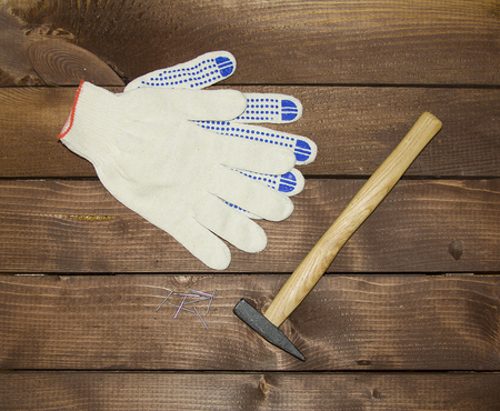 hammer and nails: hammer, nails, gloves on a wooden background, home repair