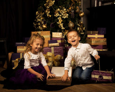 The Christmas tree is decorated with balloons and ornaments in a beautiful interior and a lot of gifts in packaging paper. A boy and a girl have fun and open gifts. Holiday, Happy New year
