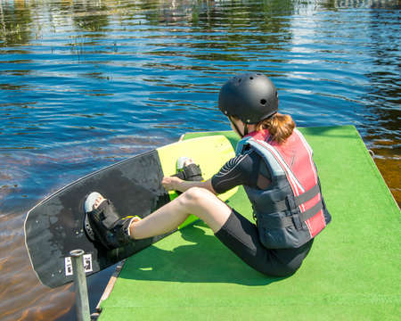 Photo 13-year-old teenage Girl in sports protective gear and helmet getting ready for training at Wake Park. Water sport. Leisure, Hobbies of teenagers. Safety in sport. Summer camp. Healthy lifestyle