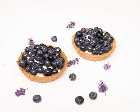 Delicious fresh dessert tartlet of shortbread decorated with blueberries among berries and lavender flowers. The concept of baking bakery, sweet food. Close-up photo, isolated, copy space.