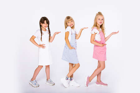 A group of children from three primary school age girls have fun on a white background in the Studio. Using hands to show the free empty copy space for item or text Banque d'images