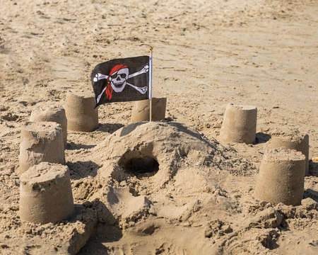 Tourism 2020, beach season. Children's figures built from sand are decorated with pirate flag. Consequences Of Covin-19. Nobody. Beach season for travelers. Games with children on the sand by the sea