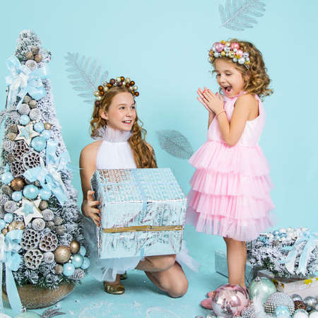 Two girls daughters sisters children received Christmas gifts in holiday boxes under Christmas tree among decorations. They are happy, laughing. New year mood, happiness, laughter. Postcard or cover