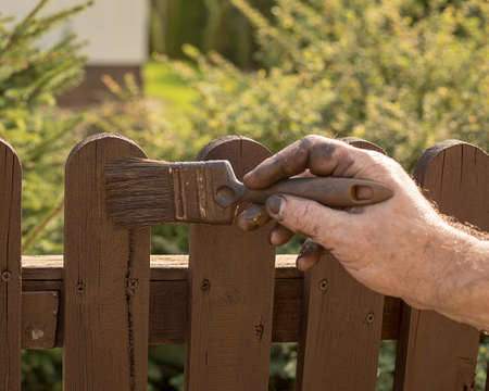 A brush in a man's hand, stained with brown paint. A man paints a wooden fence. Repair time, construction work.