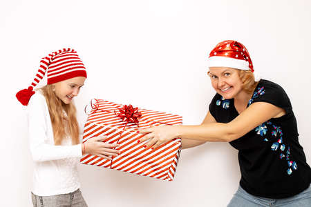 Mom and daughter girl in Santa hats are having fun on a white background, fighting for a big red gift box. Holiday concept, fun for christmas or new year. Photo Stock Photo
