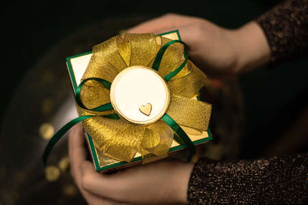 Female hands in swetear holding gift box wrapped in green paper with gold bow. Congratulations on a holiday for a man. Mock up. Copy space.