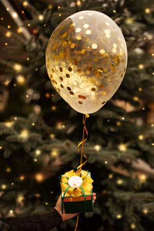close-up of womans hand holding Christmas present with balloon and decorated. Holiday consept. Christmas tree with lights in the background.
