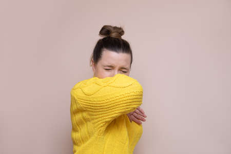 Photo of a woman in a yellow sweater with a bun on her head on a pink background. Sneezes or coughs into the elbow. Safety concept, culture of behavior