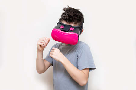 Happy teen boy wearing virtual reality watching studying movies or playing video games, studio shot. Cheerful teenager looking in pink VR glasses. Funny child experiencing 3D gadget technology in education