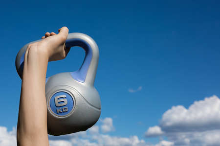 kettlebell against the sky with cloud in hand, copy space