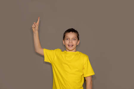 Yellow t-shirt mock up, Studio portrait of handsome young man teenager boy pointing excitedly to copyspace against gray background