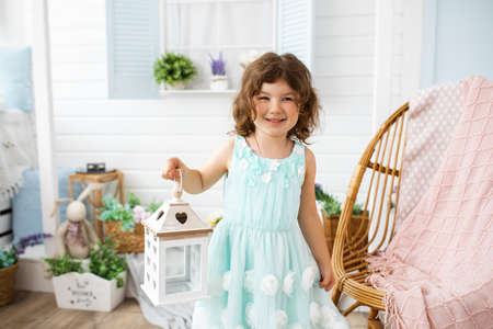 Photo of beautiful girl 4-5 years old, blue eyes, dark hair, holds white decorative lantern in her hands, smiles and looking at camera, outdoors Banque d'images