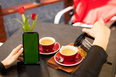 Chroma key phone screen in hands of woman drinking tea in cafe with copy space, lifestyle