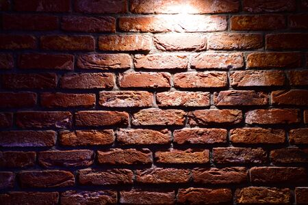 Spotlight above the Brick wall. Brick wall texture. Red brick wallpaper. Background Red Brick House Wall Texture Closeup. Red brick wall with a single light from above.