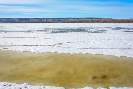 Thick ice on the river breaks into pieces under the influence of warm spring rays of the sun