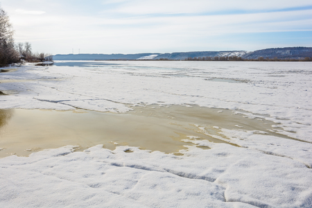 The river beach is flooded in the spring with melted snow and ice Stock Photo
