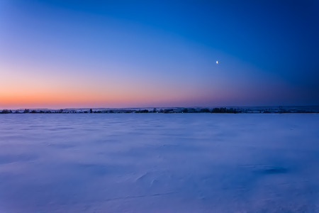 The moon and the first rays of sunlight an early winter morning