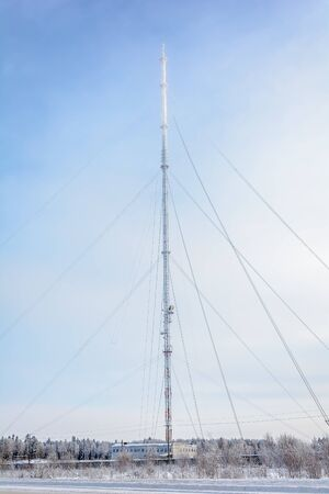 The TV tower is covered with hoarfrost, its tip rising into the fog