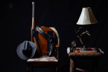 Lever action rifle, revolver, rope, cowboy hat, clock, table, lamp and a chair on black