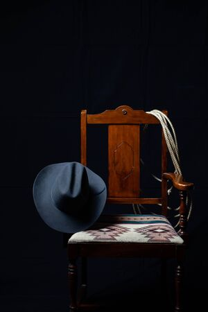 Gray cowboy hat, cattle rope and a chair on black Stock Photo
