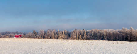 Red building next to a frost covered Wisconsin forest in January, panorama