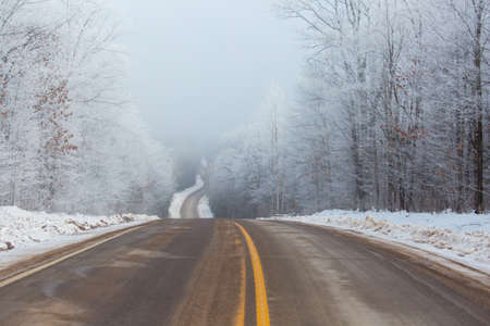 Steep hill on county highway K in Merrill, Wisconsin on a foggy winter day, horizontal