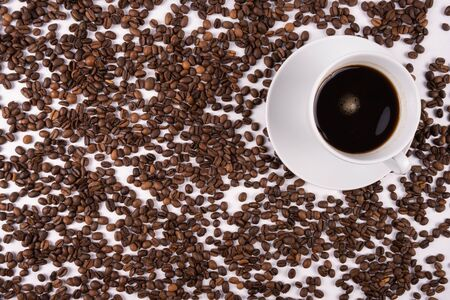 cup with coffee stands on a table, scattered coffee grains on a white background