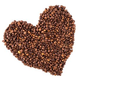 heart made of scattered coffee beans on a white background