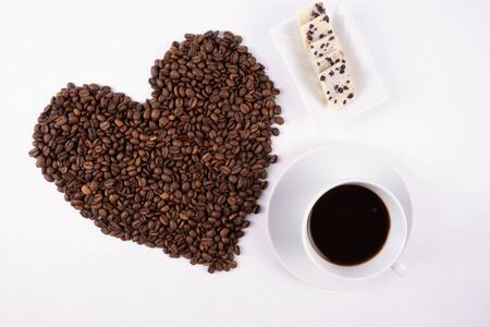 sweets, a cup of coffee and a heart made of scattered coffee beans on a white background