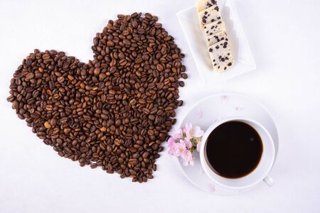 cup of coffee and heart made of scattered coffee beans on a white background