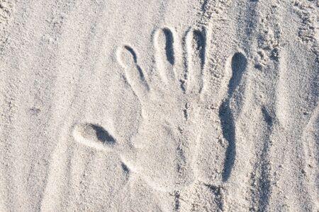 empreinte d'une main humaine sur le sable au bord de la mer Banque d'images