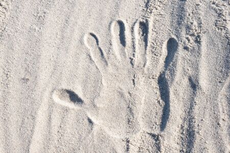 imprint of a human hand on sand by the sea