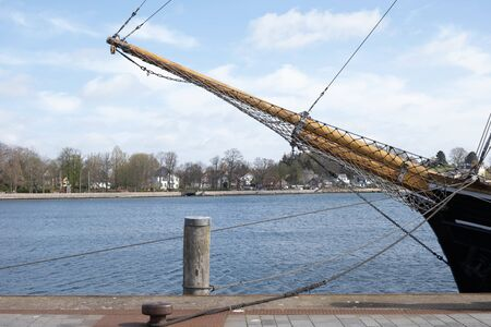 an old wooden ship docked in the port of a European city in spring