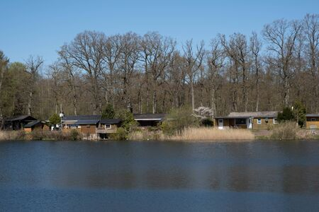 beautiful view of the wooden cottages on the lake in spring