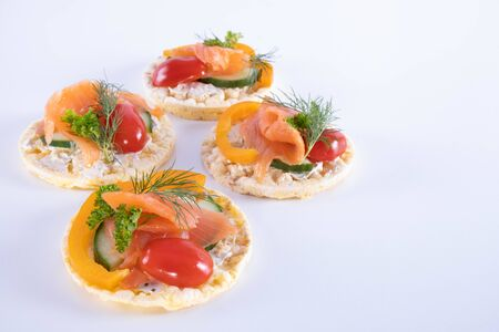 salmon, tomatoes and dill on corn waffles on a white background