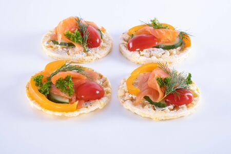 salmon, tomatoes, paprika and dill on corn waffles on a white background