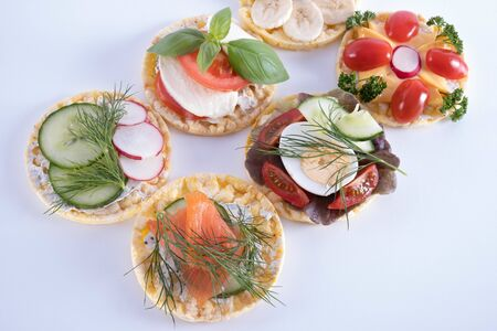 on the table are a cucumber, egg, tomatoes, bananas and radishes on corn wafers on a white background
