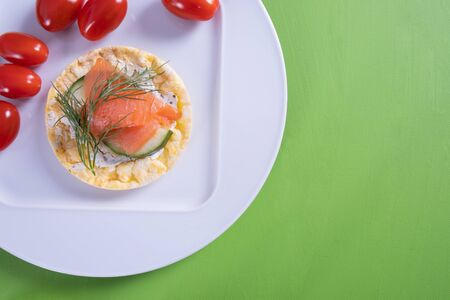 on a white plate lies a corn waffle and on it salmon, cucumber and dill on a green background