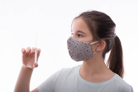 girl with a gray mask on her face holds a syringe with medicine in her hand on a white background