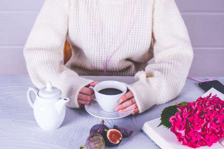 a girl is holding a cup of hot coffee in her hands, an open book is on the table and on it is a branch of pink hydrangea