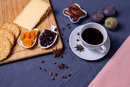 a cup of aromatic coffee, cheese, dried fruits, crackers, fresh figs, scattered coffee beans and a pink tablecloth are standing on a blue textured background