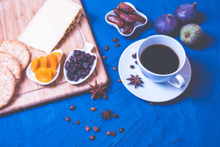 a cup of kofu, cheese, dried fruits, crackers and fresh figs on a blue texture background
