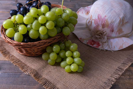 basket with grapes, on a wooden table, ripe bunches of grapes and a woman's hat Foto de archivo
