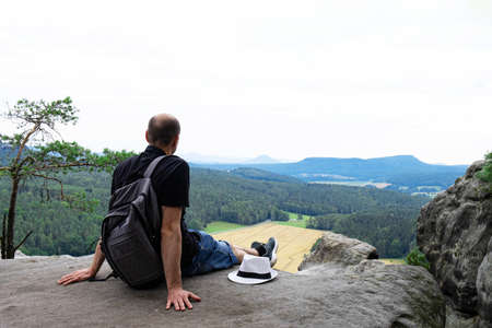 a young man sits on top of a rocky mountain, at the very edge, admires the view