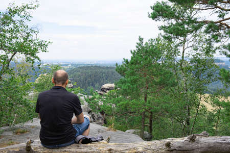 a man sits on a fallen dry tree and rests admiring the view in a high, on top of a mountain somewhere in eastern Germany