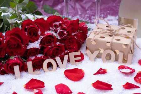 "snow, a bouquet of red roses, a bottle of champagne and the inscription ""I love you"" on a pink background"