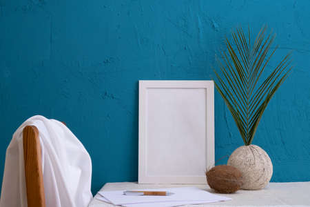 coconut, fern in an old vase, set for writing, white photo frame on a blue background on the table