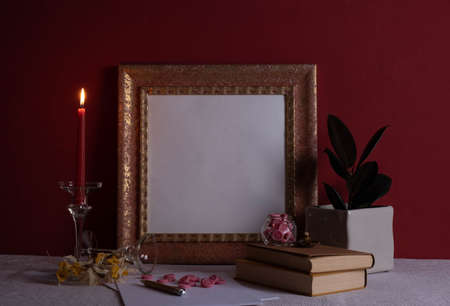 houseplant, candlestick on a long leg with a burning candle, old books, old photo frame on a red background on the table Zdjęcie Seryjne
