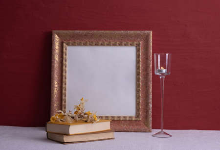 books, dry daffodils, a long-stemmed candlestick, an old photo frame on a red background on the table